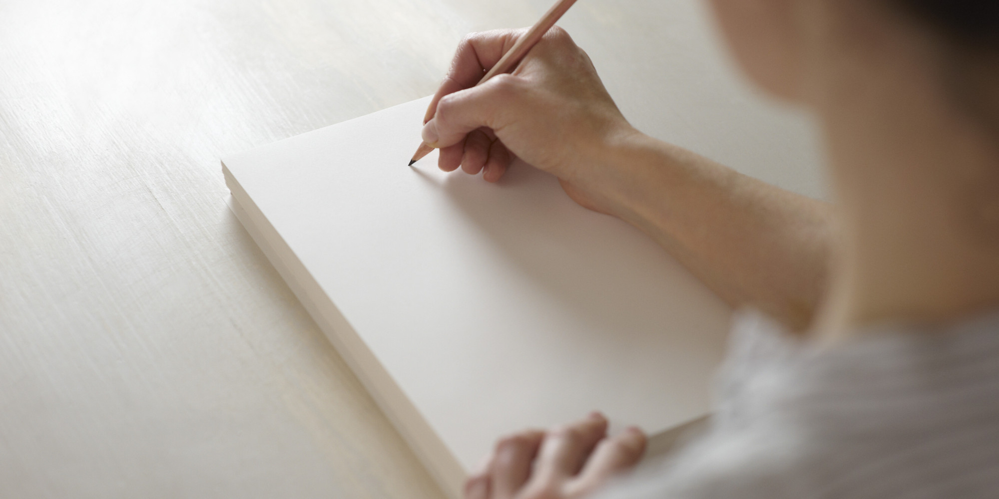 Woman about to draw on blank pad of paper